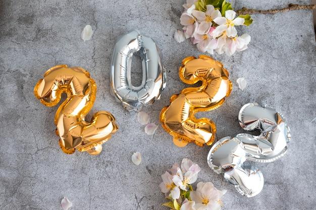 Números de globos de lámina de oro y plata sobre un hormigón