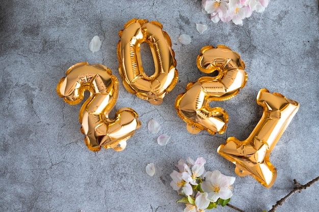Números de globos de lámina de oro y ramas de flores de manzana en un hormigón