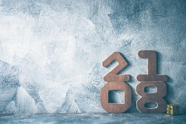 Números de madera 2018 en fondo gris del grunge. feliz año nuevo concepto. espacio libre para texto