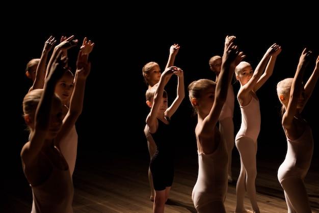 Un numeroso grupo de niños ensayando y bailando el ballet.