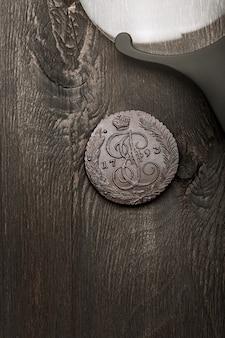 Numismática. moneda de colección antigua y lupa sobre una vieja mesa de madera. fondo oscuro. vista superior.