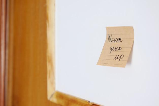 Nunca renuncie a la palabra en una nota adhesiva en una pizarra blanca