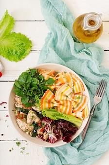 Nutrición apropiada. ensalada dietética farfalle pasta trigo duro con filete de pollo al horno con berenjenas, calabacín y ensalada en un tazón. vista superior. lay flat