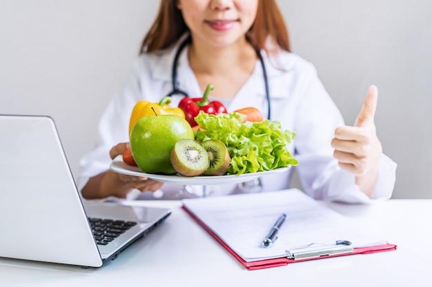 Nutricionista dando consulta al paciente con frutas y verduras saludables, nutrición adecuada y concepto de dieta