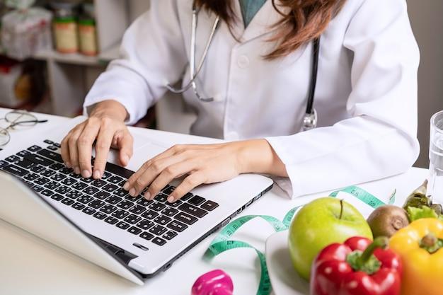 Nutricionista dando consulta al paciente con frutas y verduras saludables