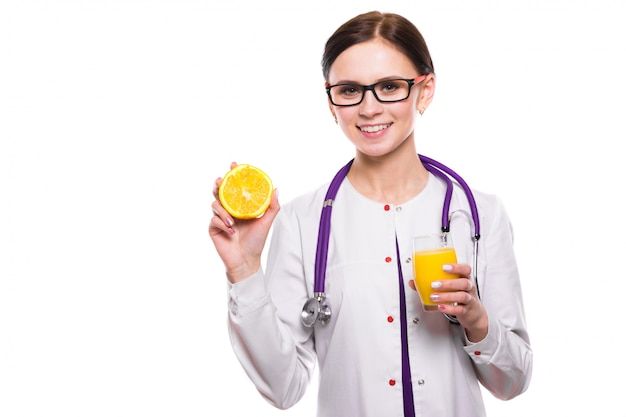 Nutricionista femenina mantenga naranja en la sección y vaso de jugo fresco en sus manos en blanco