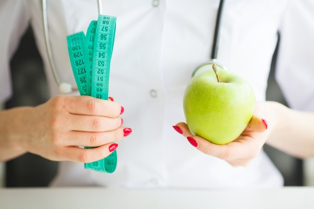 Nutricionista femenina y sosteniendo una manzana y una cinta métrica.