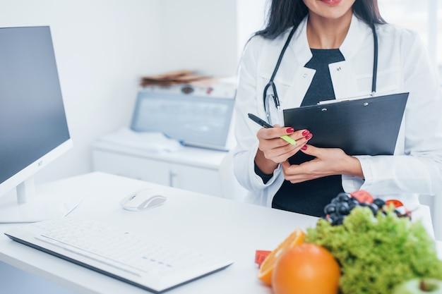 Nutricionista mujer en bata blanca sentado en el interior de la oficina en el lugar de trabajo.