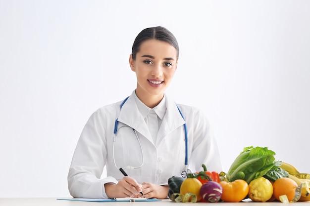 Nutricionista mujer sentada a la mesa con portapapeles y productos saludables sobre fondo blanco.