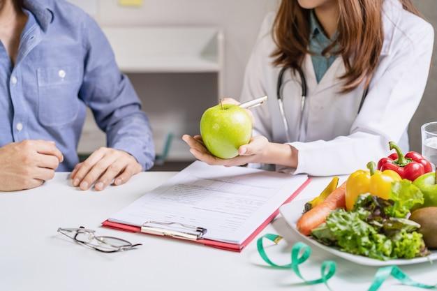 Nutricionista que consulta al paciente con frutas y verduras saludables, nutrición adecuada y concepto de dieta