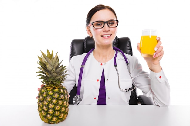 Nutricionista de sexo femenino que se sienta en su lugar de trabajo que muestra y que ofrece el vidrio de jugo fresco de la piña que sostiene la piña en su mano en blanco