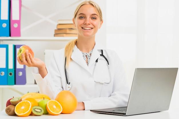 Nutricionista sonriente de tiro medio con manzana
