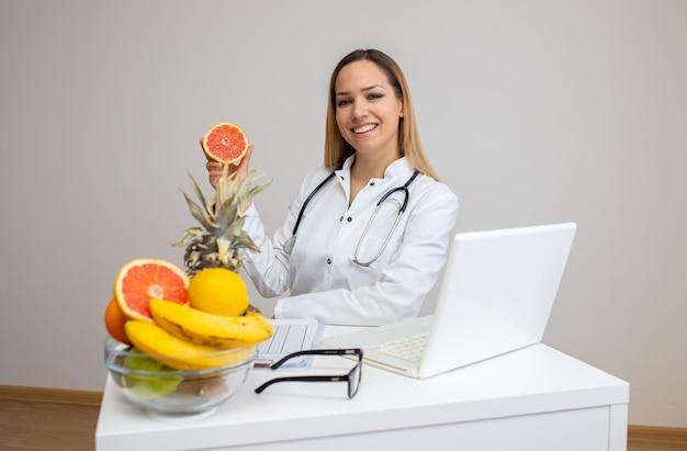 Nutricionista en su oficina mostrando frutas saludables