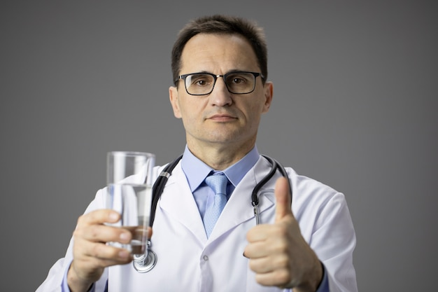 Nutricionista tiene agua de vidrio. estilo de vida saludable. balance de agua. pulgar arriba. me gusta