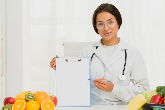 Nutricionista de tiro medio sosteniendo un portapapeles