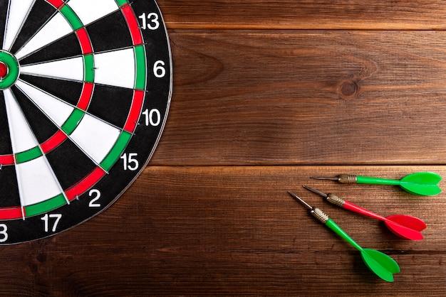 Objetivo de dardos aislado en dardos de madera y tricolores. golpea el objetivo