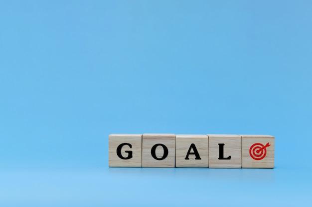 Objetivo empresarial. objetivo palabra escrita en la pila de bloques de cubos de madera sobre fondo azul, felicitación de año nuevo, tendencia, idea, finanzas, estrategia, negocios, marketing online, objetivo y concepto de plan de destino
