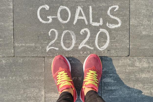 Objetivos 2020 escritos en la acera gris con piernas de mujer en zapatillas de deporte