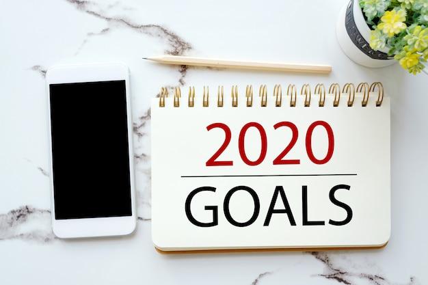 Objetivos 2020 en papel de nota y teléfono con pantalla en blanco