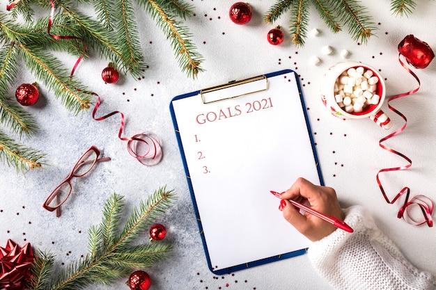 Objetivos de año nuevo 2021. mano de mujer escribe pluma de ideas en el cuaderno. vista superior