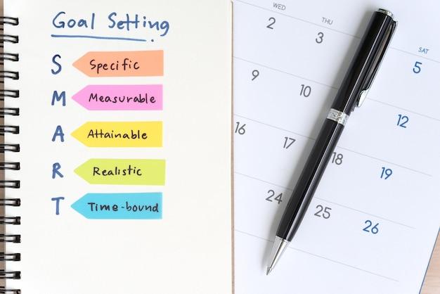Objetivos inteligentes que fijan acrónimos en el cuaderno con el calendario