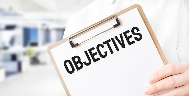 Objetivos del texto en la placa de papel blanco en manos del empresario en la oficina. concepto de negocio