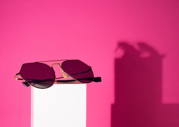 Objeto del artilugio de las gafas de sol de la moda en el polo blanco con el fondo rosado del color