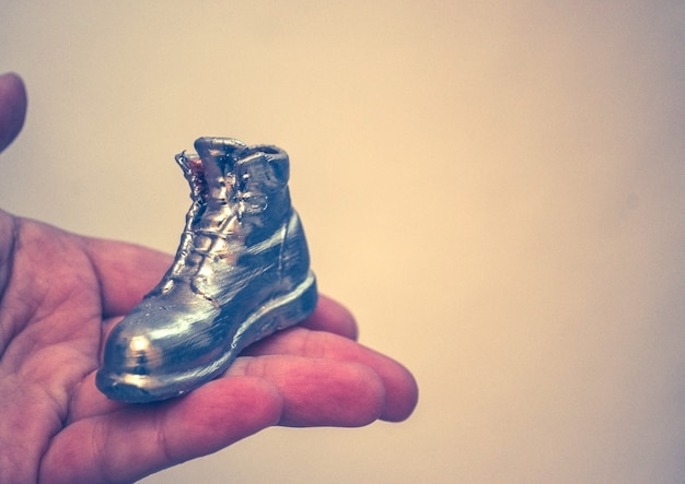 Objeto en forma de bota impreso en una impresora 3d y cubierto con esmalte en primer plano de la mano. aislado sobre fondo blanco. tecnología aditiva moderna progresiva. copiar spase