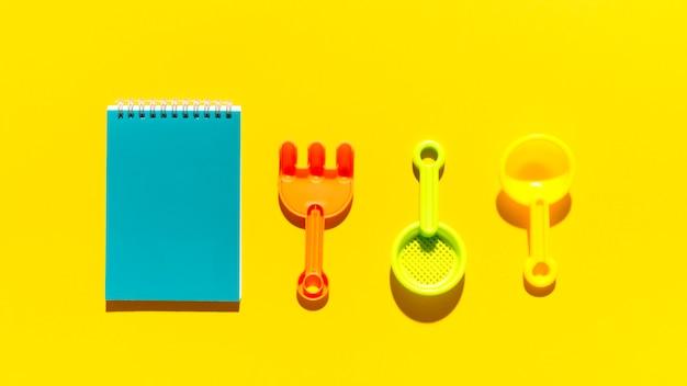 Objetos de la caja de arena de verano y bloc de notas en superficie brillante
