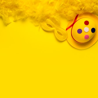 Objetos de carnaval con boa de plumas amarillas y espacio de copia