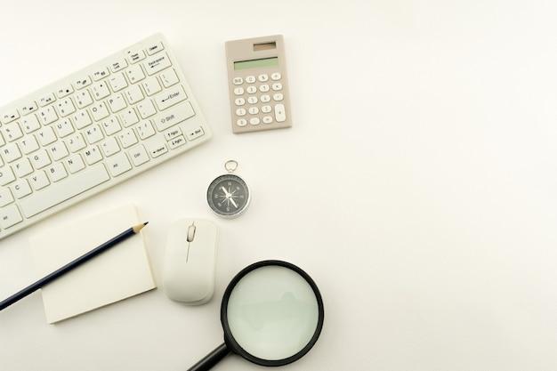 Objetos comerciales de pc, teclado, mouse, lápiz, brújula y calculadora, lupa sobre fondo blanco de mesa.