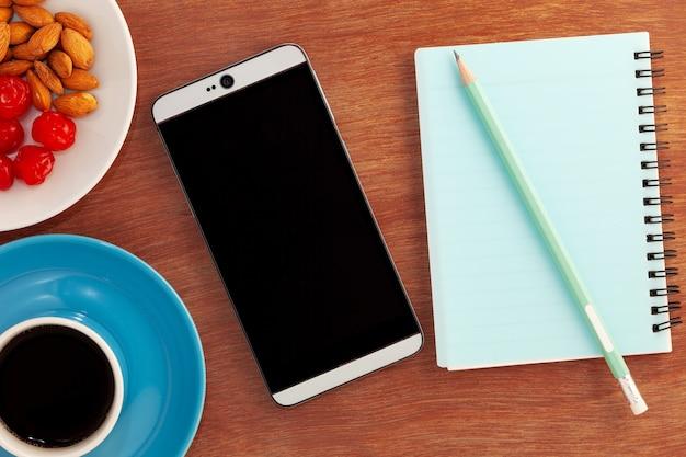 Objetos de negocios de taza de café con teléfono inteligente, nota de papel, almendra, cereza y lápiz