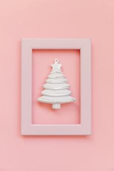 Objetos de invierno adorno abeto en marco rosa aislado sobre fondo rosa