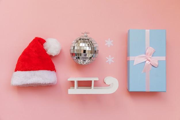 Los objetos de invierno de composición simplemente mínima adornan la caja de regalo del trineo del sombrero de santa aislada en el fondo rosado de moda en colores pastel