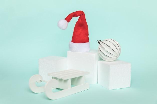 Objetos de invierno de composición simplemente mínima adorno y formas de cubo forma geométrica podio aislado fondo azul pastel. navidad año nuevo diciembre tiempo por concepto de celebración. maqueta, espacio de copia