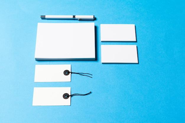 Objetos de oficina en blanco organizados para la presentación de la empresa sobre fondo de papel azul