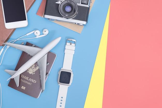 Objetos de viaje y accesorios sobre fondo azul amarillo rosa con cámara de pasaporte y avión