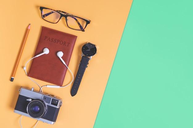 Objetos de viaje y accesorios sobre fondo naranja púrpura verde marrón con cámara de pasaporte