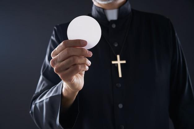 Oblea de comunión hostia sacerdote en las manos.
