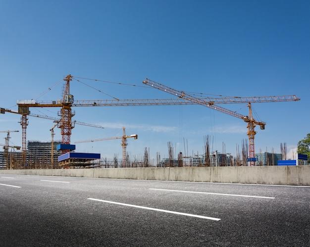 Obras de construcción con grúas contra el cielo azul