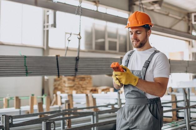 Obrero en la casa de la tienda en casco naranja