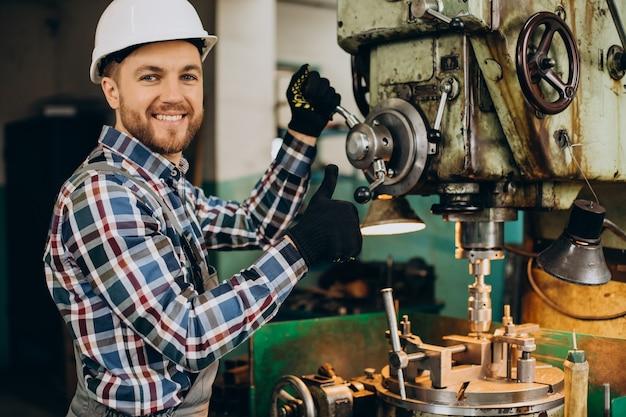 Obrero con casco trabajando con construcciones metálicas en la fábrica.
