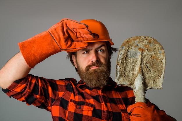 Obrero con pala constructor en guantes de trabajo mantenga pala constructor de concepto de tecnología de la industria de la construcción en