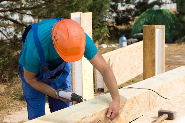 Obrero perforando un agujero en una viga aislada revestida de madera en un sitio de construcción de nueva construcción para una nueva casa