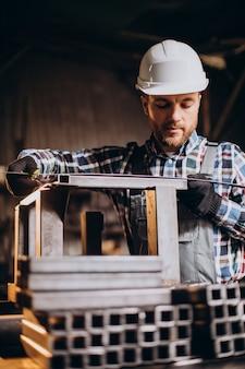 Obrero vistiendo har hat con regla de medición en la fábrica.