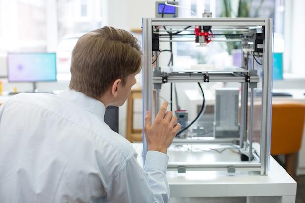 Observación minuciosa. joven de pelo castaño de pie de espaldas a la cámara y mirando una impresora 3d trabajando