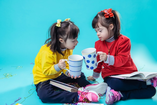 Observando el libro para adultos. hermanitas despreocupadas con trastorno mental que tintinean tazas gigantes mientras leen libros