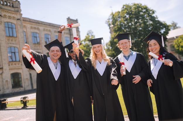 Obtención de la maestría. cinco estudiantes alegres parados juntos en el campus celebrando su graduación de la universidad.