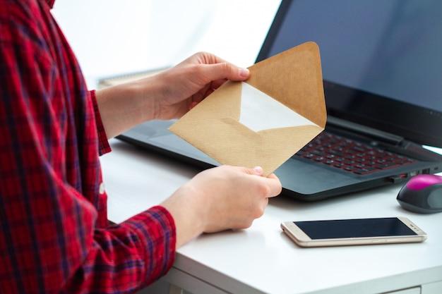 Obtenga el mensaje escrito y abra el sobre con una carta. recibir y enviar correspondencia por escrito.