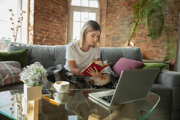 Obteniendo tareas. mujer caucásica, autónoma durante el trabajo en la oficina en casa mientras está en cuarentena. joven empresaria en casa, auto aislado. usando gadgets. trabajo remoto, prevención de la propagación del coronavirus.